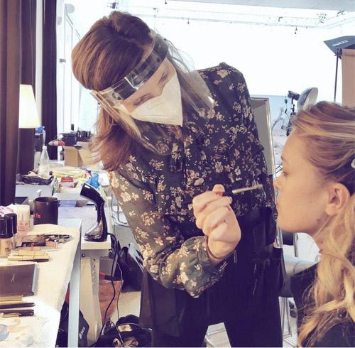 Frau in Corona Schutzkleidung: Gesichtsschild, Mundnasenschutz vor einem beleuchteten Kosmetikspiegel und Model